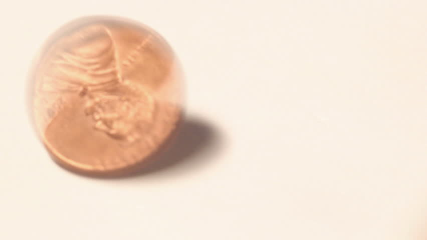 Close up of a spinning United States One Cent piece (penny) and coming to a stop heads up on a white background.