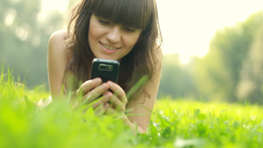 Young woman lying on the grass and sending sms, texting in the park | Shutterstock HD Video #1341550