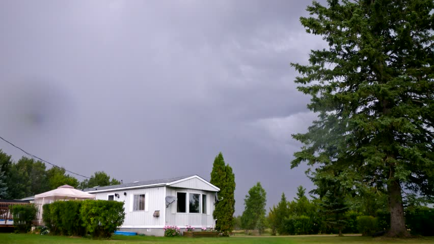 small home weathers a rain storm and the clouds swirl overhead