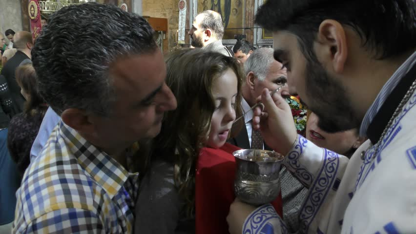 LOD, ISRAEL - DECEMBER 16, 2015: A priest administers communion during the Celebration and Mass of St. George the Dragon Slayer Day in the Greek Orthodox Church for local and Arab Christians | Shutterstock HD Video #13440620