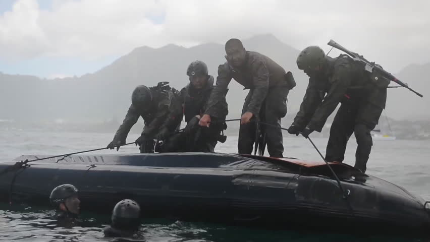 CIRCA 2010s - Navy Seals train on rubber zodiac watercraft while a helicopter performs a helicasting maneuver.