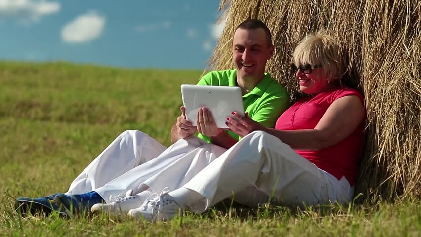 Man and woman with Tablet-PC sits near a haystack. Mother and son with tablet computer looks and flips through the photos on tablet computer | Shutterstock HD Video #13499696