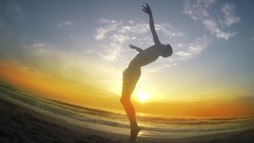 trace shows various jumps while running on beach sunset sand, backflip, cartwheel, SLOW MOTION