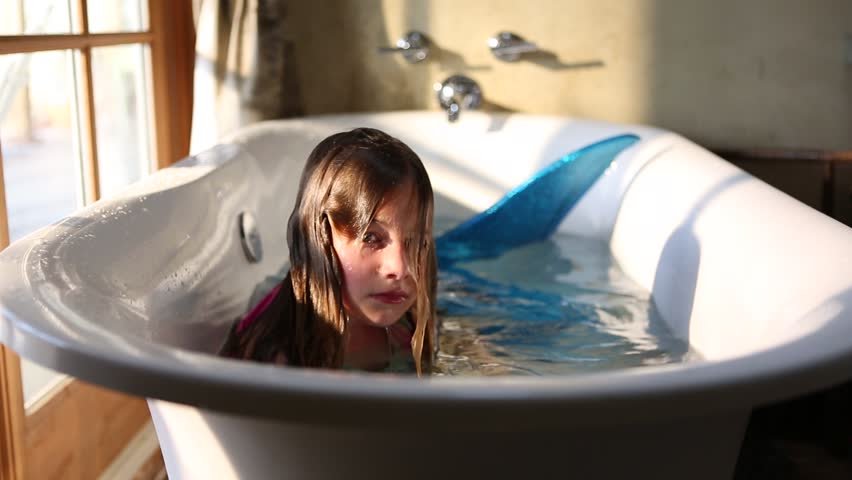 9 year old girl with fake mermaid costume in bathtub