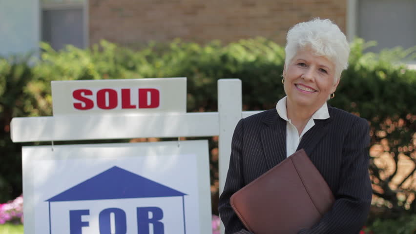 Real estate agent in front of a sold house