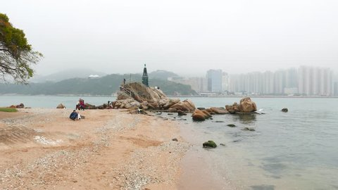 HONG KONG - FEBRUARY 22, 2015: Sea channel, sandy beach and small lighthouse on rocks, cloudy weather. Camera pan left, show beautiful landscape of Lei Yue Mun, Kwun Tong, Hong Kong