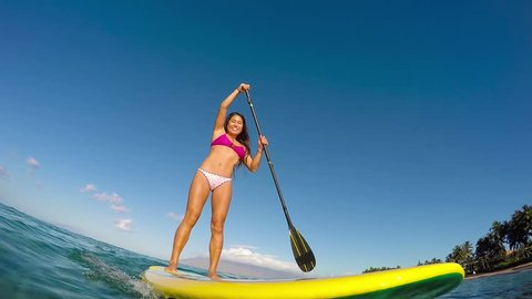 Active Woman Stand Up Paddle Boarding On Summer Day