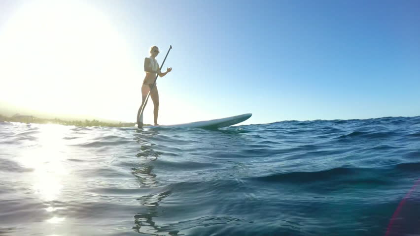 Young Attractive Woman Stand Up Paddle Boarding in Blue Ocean