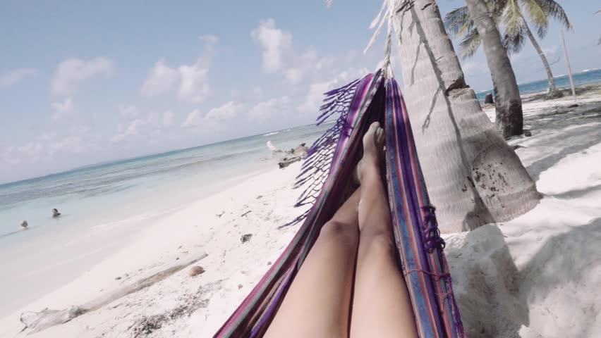 Hispanic woman relaxing in hammock on caribbean beach at San Blas islands, Panama