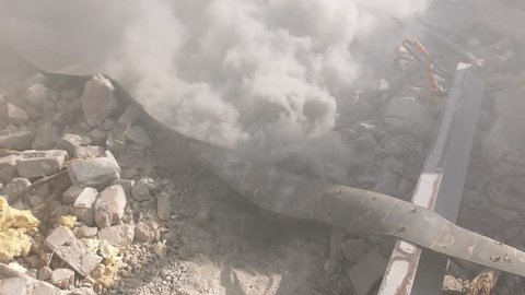 Smoke comes out of the rubble as a result from earthquake rocket attack tsunami demolition
