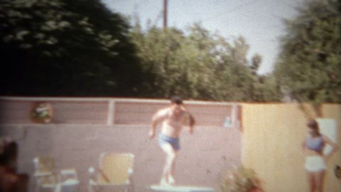 SAN DIEGO, CALIFORNIA 1965: Man falls off springboard in failed attempt at pool diving fun.
