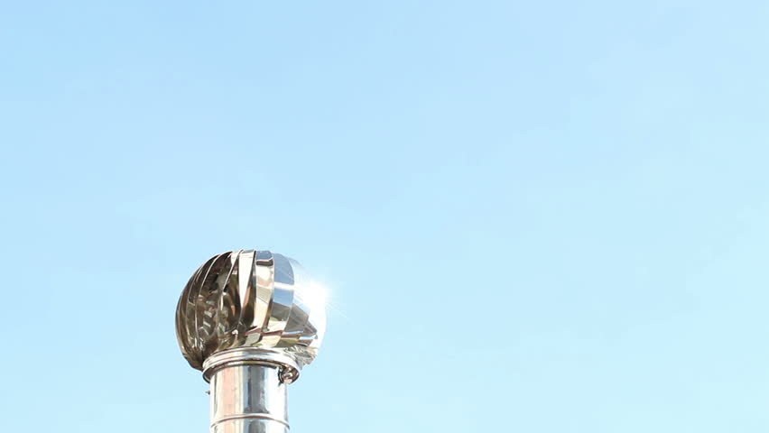 A view of a roof ventilator in motion against a brilliant blue sky