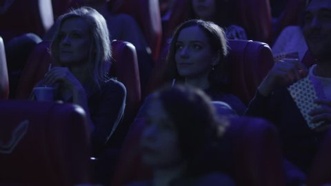 Group of people are watching a film screening in a movie cinema theater. Shot on RED Cinema Camera in 4K (UHD).
