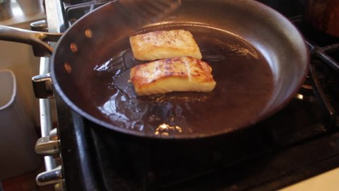 white fish fillets cooking on stove, flipped with spatulas