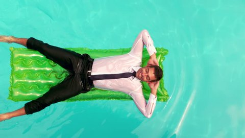 Wet businessman relaxing on inflatable in slow motion