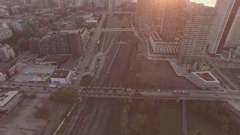 4k Aerial shot train tracks overlooking downtown Toronto camera following train during sunrise