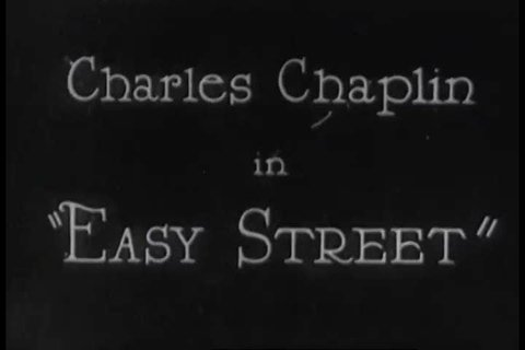 CIRCA 1920s - A clip of Charlie Chaplin in the silent film, Easy Street in 1920s, shows Charlie trying to free someone's head from inside a lamppost.