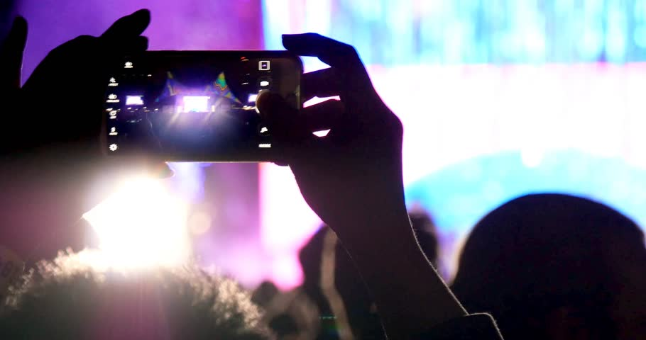Fan person taking video and photos on mobile smart phone at concert party crowd cheering at rock music event with flashing light show and band on stage.