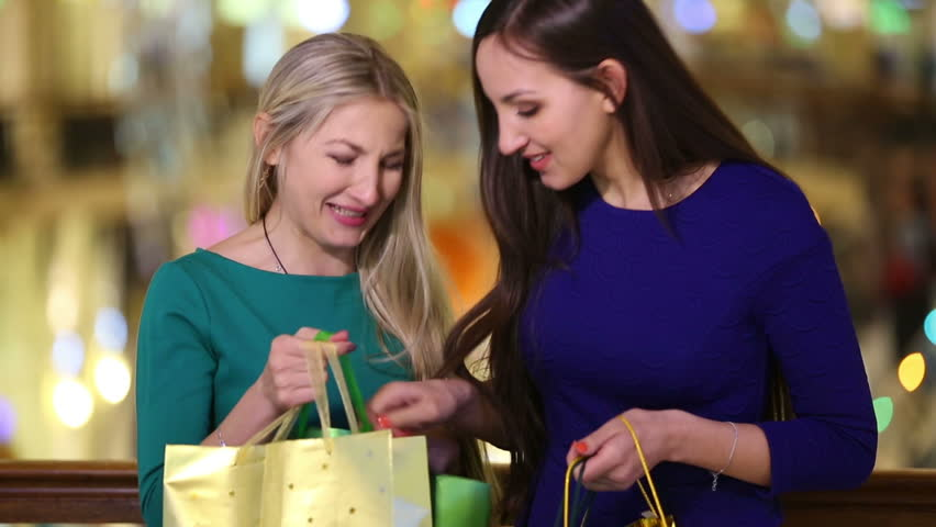 Two Girls A Blonde And Brunette Consider Their Purchases At The Mall