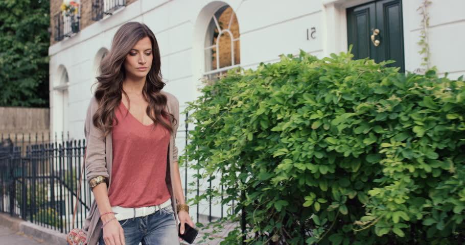 Beautiful woman using smart phone technology app walking through city streets living urban happy lifestyle | Shutterstock HD Video #13909100
