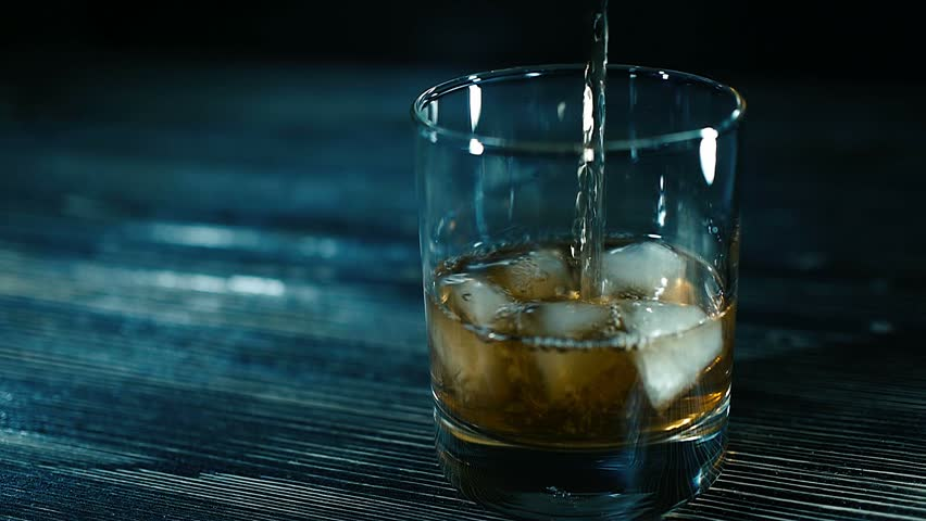whiskey on the rocks poured from a bottle - alcohol, bar Whiskey pouring into a glass with ice