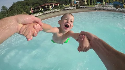 SLOW MOTION POV: Playful father spinning his child, happy little boy is laughing and screaming in sunny summer