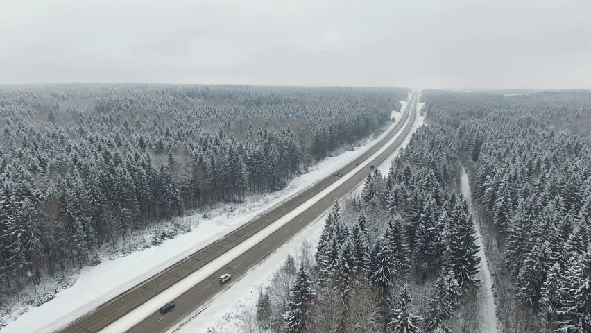 4K. Road in the winter forest with driving cars. Aerial panoramic view. Vanishing point perspective.