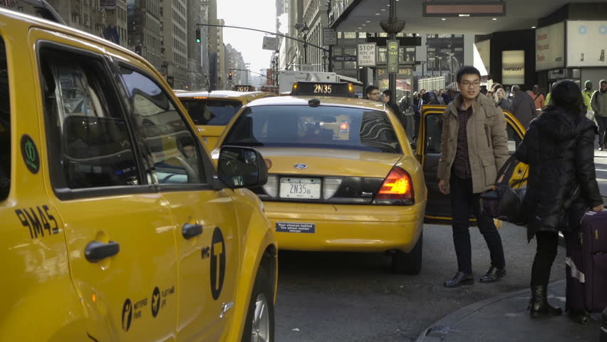 NEW YORK - DEC 16, 2015: Asian man saying goodbye mother luggage and getting into yellow taxi cab NYC. Manhattan has a huge tourism industry. | Shutterstock HD Video #13940030