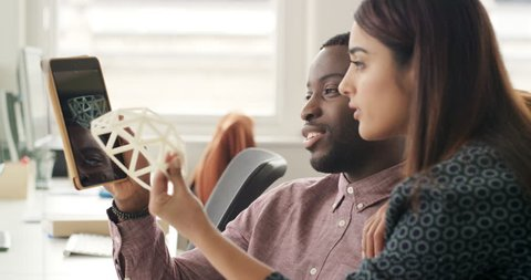 Female engineer showing 3d printed object in Creative business team meeting in modern start up office team leader pointing at screen discussing geodesic dome shape