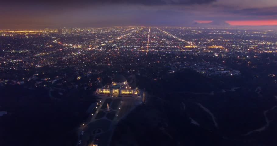 Aerial view of illuminated Los Angeles cityscape at night with Griffith Observatory in foreground. 4K UHD.