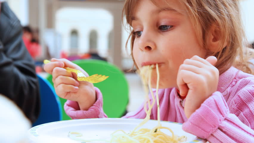 small pretty girl with yellow fork in hands eats pasta, close-up