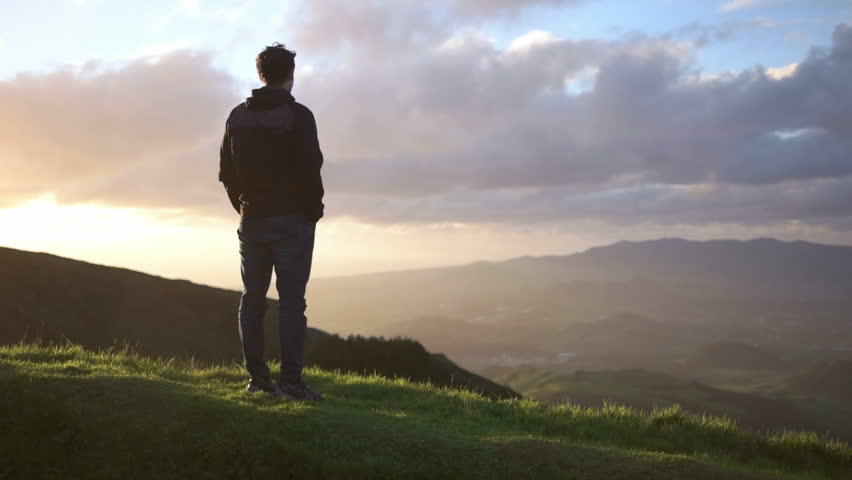 Young caucasian man looking down from the mountaine towards the ocean | Shutterstock HD Video #13997699