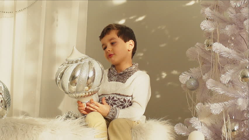 A cute little boy sits on a bed and holds a big balloon on New year    Shutterstock HD Video #14010440