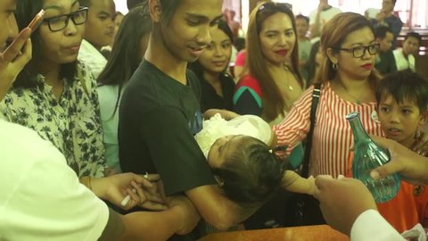 SAN PABLO CITY, LAGUNA, PHILIPPINES - JANUARY 13, 2016: The Holy Catholic rite of the sacrament of baptism of young baby in a Christian church, a religious requirement.