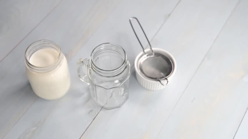 Making Kefir: Close up of hands filtering kefir grains from kefir and pouring into glass jar | Shutterstock HD Video #14034530