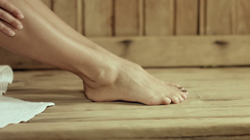 Beautiful well-groomed woman's bare feet in the sauna, girl rubbed oil into the skin