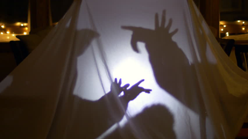 Two Children Playing Shadow Puppets In Home Made Tent