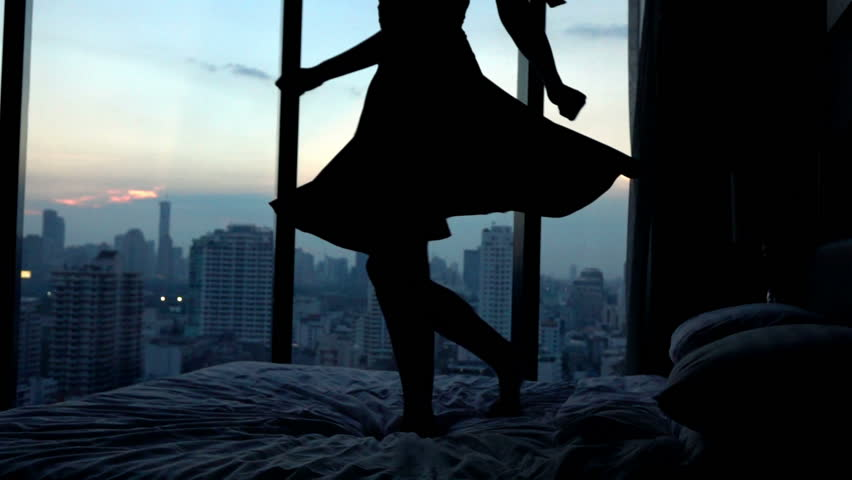 Young happy woman in dress dancing on hotel bed, super slow motion, 240fps