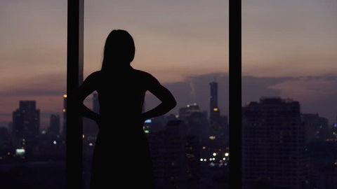 Young woman looking at cityscape by the window at night