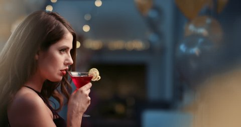 Beautiful woman drinking cocktail alone at glamorous party sad and alone at sexy fashion new year's eve event