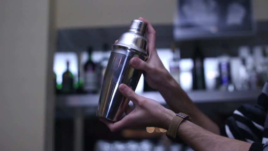 Close up shot of a bartender shaking a drink in a cocktail shaker.