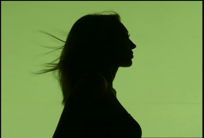 A silhouetted woman dancing against green background