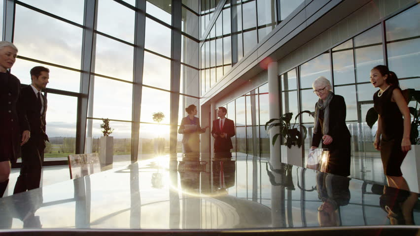 4k / Ultra HD version A confident and happy business team take their seats at a long reflective conference table. They are in an office and the interior panels of glass are reflecting the clouds  | Shutterstock HD Video #14127455