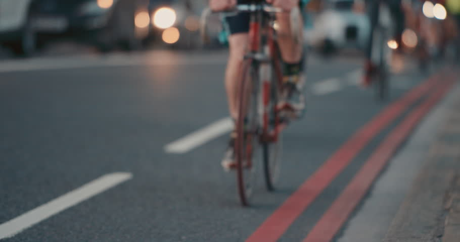Anonymous crowd of people walking cycling bicycles commuters London City street slow motion