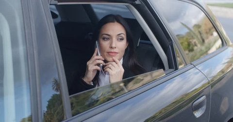 Laughing young executive on phone in car