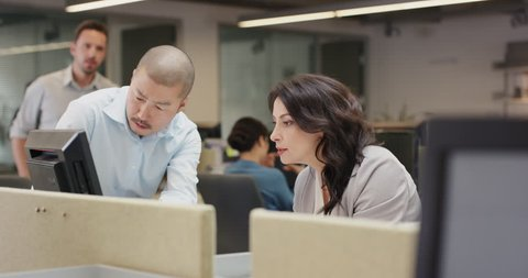 Woman manager leading diverse team meeting in small business. Three people working around computer late at night