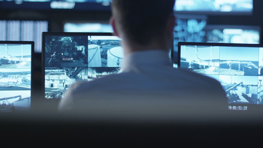 Security officer is working on a computer in a dark monitoring room filled with display screens. Shot on RED Cinema Camera in 4K (UHD).