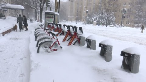 WASHINGTON, DC - JAN. 23, 2016: Bike Share bikes in snow storm, tow truck passes, dog walkers, as Blizzard subsides. The 2-day snow storm dumped two feet of snow on the city, closing much of it down