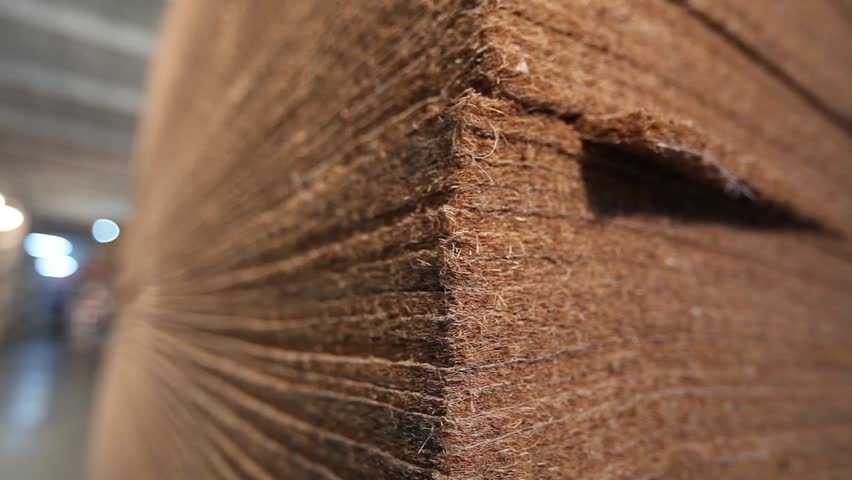 The warehouse of raw materials, sheets of coconut fiber, coir sheets for mattresses, sheets of coconut fiber in stock, racks with fabrics, Industrial interior, warehouse interior, fabric warehouse,