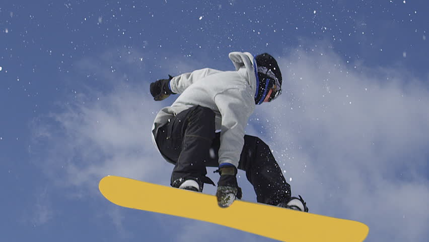 SLOW MOTION CLOSE UP: Snowboarder jumping over the camera spinning